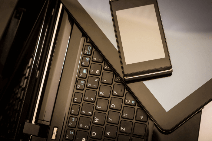 Cell phone and tablet stacked on top of a laptop