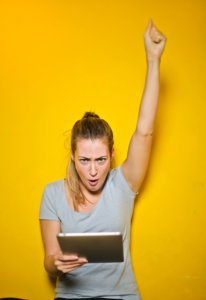 Woman holding an iPad and raising her fist triumphantly